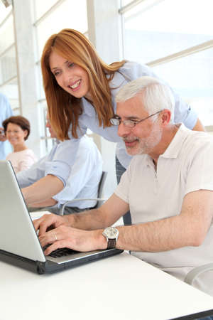 explaining: Senior man with trainer in front of laptop computer Stock Photo