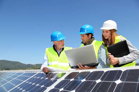 photovoltaic panel: Group of engineers meeting on building roof