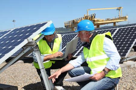 safety check: Ingenieros de comprobaci�n de paneles solares en ejecuci�n Foto de archivo