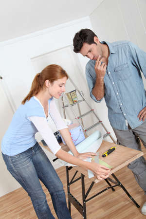 Couple choosing wallpaper color for new house photo