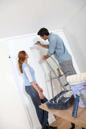 Young couple painting walls of their new house photo