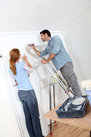 reforming: Young couple painting walls of their new house Stock Photo