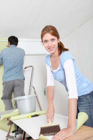 Couple putting new wallpaper in room photo