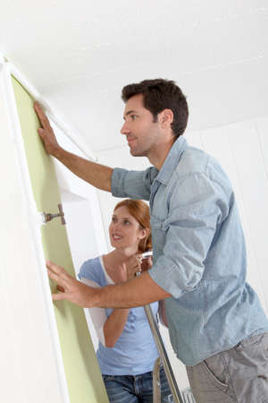 reforming: Couple putting new wallpaper in room
