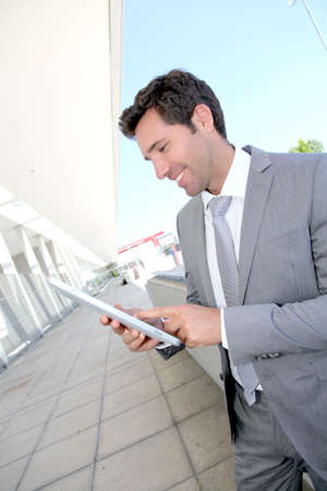 android tablet: Businessman using electronic tablet outside a building Stock Photo
