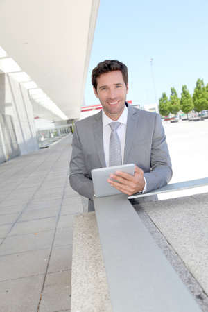 Businessman using electronic tablet outside a building photo