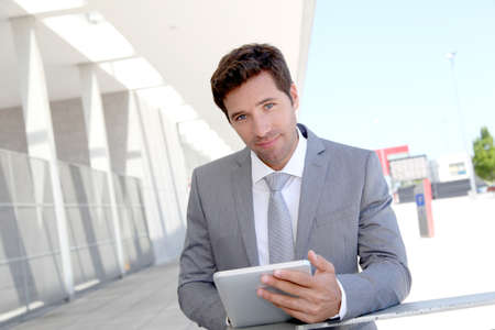 tradeshow: Businessman using electronic tablet outside a building Stock Photo