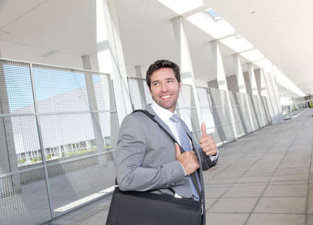 Businessman standing with briefcase photo