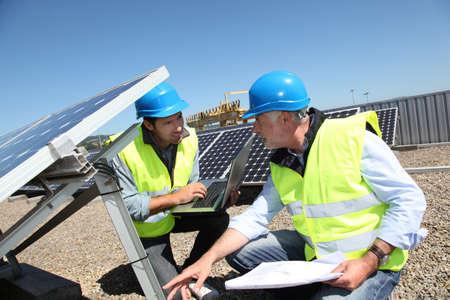 arrodillarse: Ingenieros de comprobaci�n de paneles solares en ejecuci�n Foto de archivo