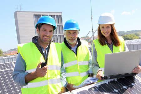 energ�as renovables: Grupo de ingenieros reunidos en la construcci�n de techo
