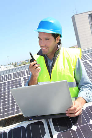 Engineer with walkie-talkie on photovoltaic installation photo