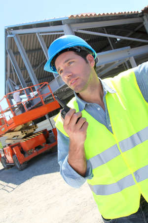 buildingsite: Foreman using walkie-talkie on construction site