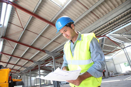 building safety: Engineer checking plan in building under construction