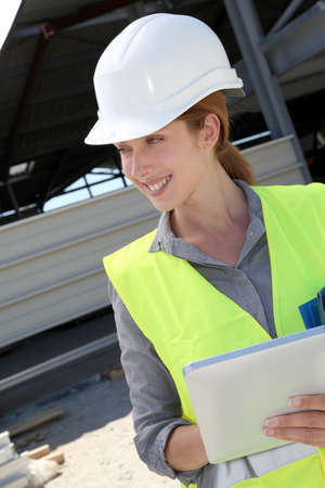 buildingsite: Woman engineer checking building plan on touchpad Stock Photo