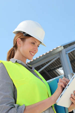 Woman engineer checking building plan on touchpad photo