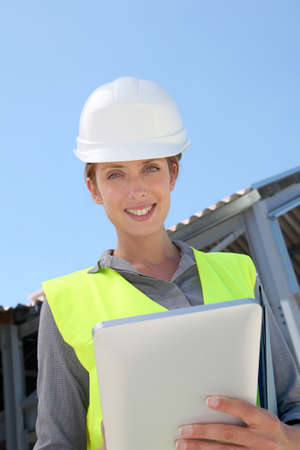 Woman engineer checking building plan on touchpad Stock Photo - 9635008