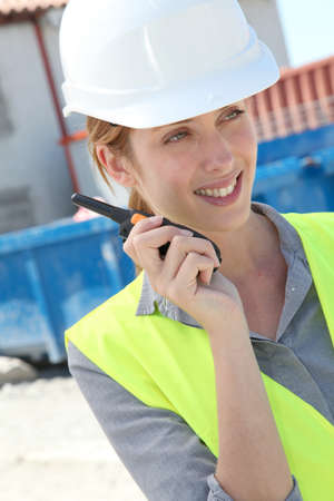 Woman using walkie-talkie on construction site photo