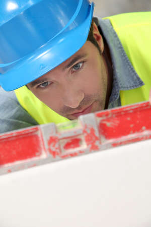 lifevest: Worker using level on building site Stock Photo