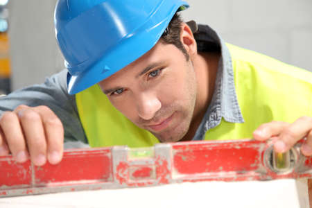 Worker using level on building site Stock Photo