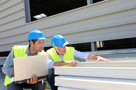 Construction workers checking building material Stock Photo - 9635042