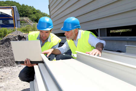 building material: Construction workers checking building material