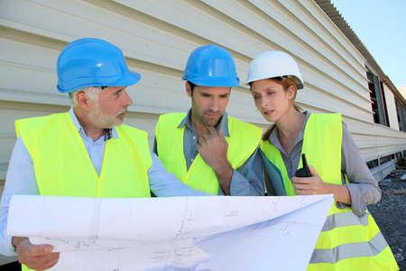 workteam: Workteam checking plan on construction site Stock Photo