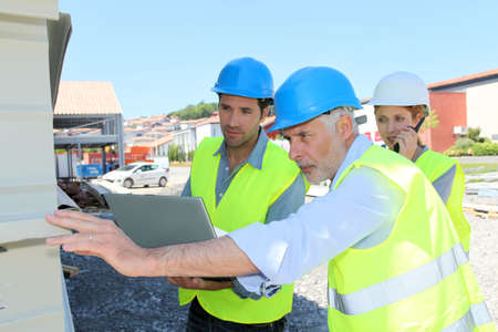 Construction workers checking building structure photo