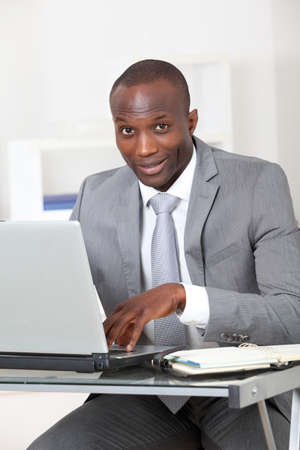 africanamerican: Businessman sitting at his desk in office Stock Photo