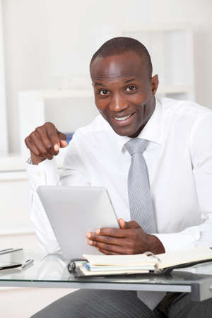 Businessman using electronic tablet in office photo
