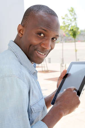 Man in urban area using electronic tablet photo