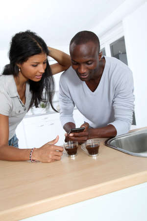 Cheerful couple using smartphone while taking coffee photo