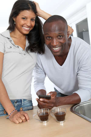 Cheerful couple using smartphone while taking coffee Stock Photo - 9638836
