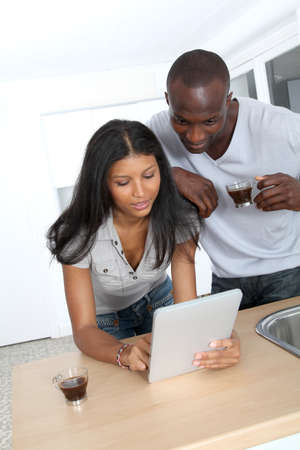 Young couple using electronic pad in kitchen photo