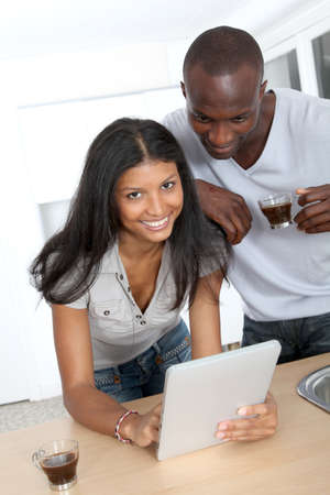 Young couple using electronic pad in kitchen Stock Photo - 9638012