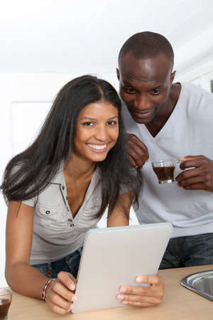 electronic pad: Young couple using electronic pad in kitchen Stock Photo