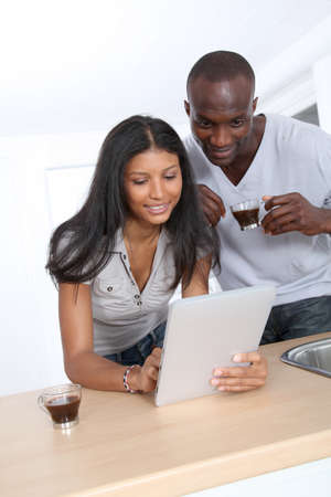 Young couple using electronic pad in kitchen Stock Photo - 9635505