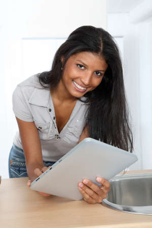 Young latin woman using electronic tablet in home kitchen photo