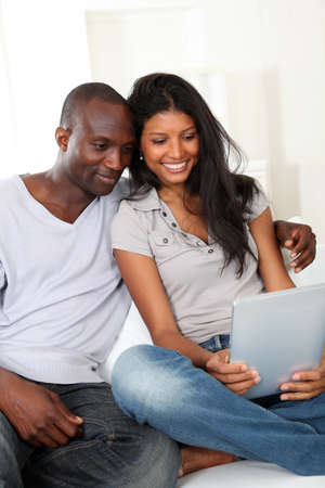 Happy loving couple sitting in sofa with electronic tablet  photo