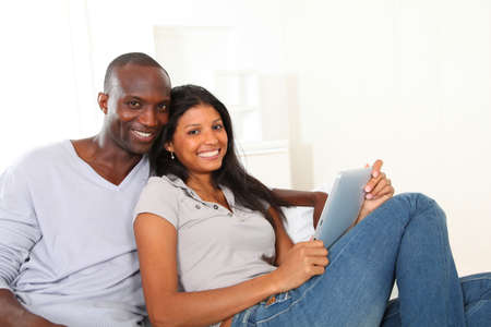 grownups: Happy loving couple sitting in sofa with electronic tablet  Stock Photo