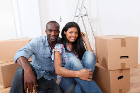 Cheerful couple sitting in empty new house photo