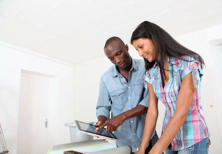 Couple choosing wallpaper for new home photo