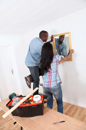 Young couple hanging mirror on the wall Stock Photo - 9784667