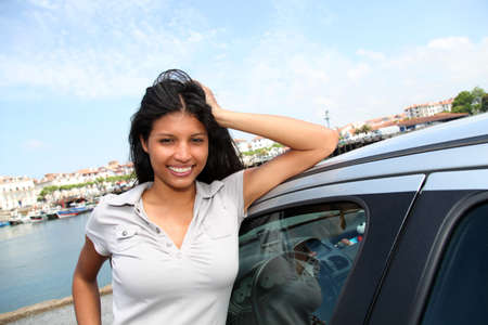 Smiling girl standing by car in tourist town photo