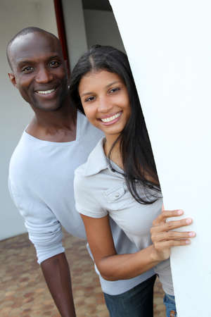 Cheerful couple standing by house entrance door photo