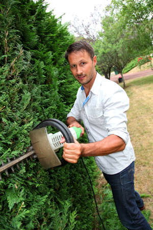 40 years old man: Man in private garden cutting bushes