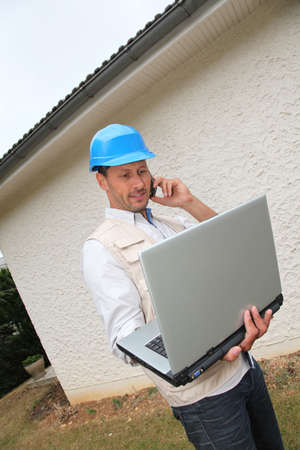 Entrepreneur using telephone and laptop computer photo