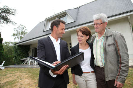 Real-estate agent with senior couple buying new house photo