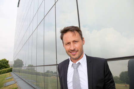 Portrait of businessman standing in front of modern building photo