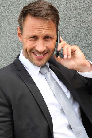 Portrait of handsome businessman talking on mobile phone photo