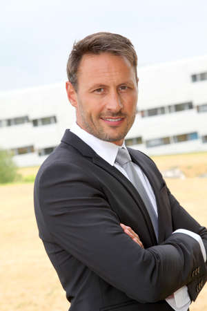 Portrait of smiling businessman in dark suit Stock Photo - 9784578